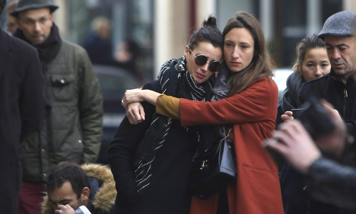Women comfort each other as they stand in front of the Carillon cafe, in Paris, Nov. 14, 2015. French President Francois Hollande vowed to attack Islamic State without mercy as the jihadist group admitted responsibility Saturday for orchestrating the deadliest attacks inflicted on France since World War II. (AP Photo/Thibault Camus)