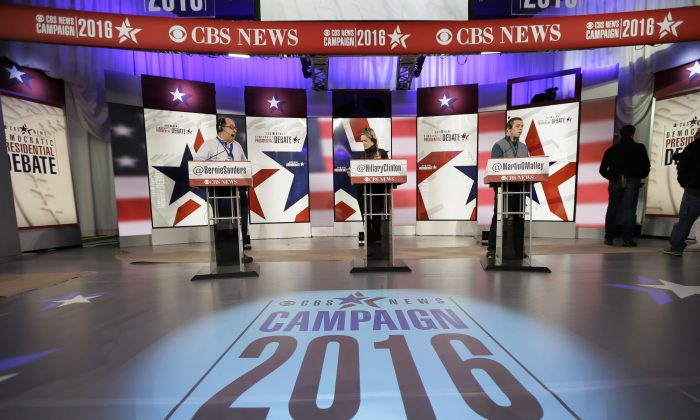 Workers stand at the podiums on stage during final preparations for Saturday night's Democratic presidential debate between Sen. Bernie Sanders (I-Vt.), Hillary Rodham Clinton and former Maryland Gov. Martin O'Malley, in Des Moines, Iowa, on Nov. 13, 2015. (AP Photo/Charlie Neibergall)