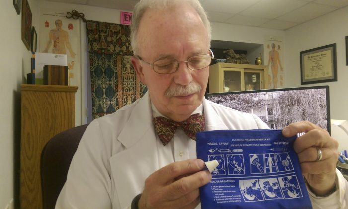 Dr. John Aldis holds a noloxone nasal spray kit with the instruction sheet in Martinsburg, W.Va., on Nov. 3, 2015. Aldis trains people so that they can administer noloxone to an individual who's having a heroin overdose. (Jenni Vincent/The Journal via AP)