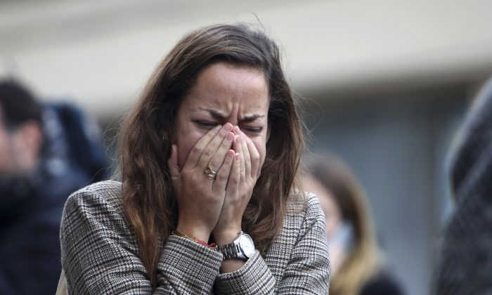 A woman reacts as she stands outside Le Carillon restaurant in Paris on Nov. 14, 2015. At least 129 people died and 352 were hurt Friday night in shootings at Paris cafes, suicide bombings near France's national stadium and a hostage-taking slaughter inside a concert hall. (Steve Parsons PA via AP)