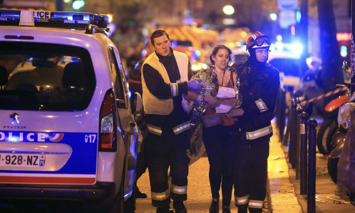 Rescue workers help a woman after a shooting, outside the Bataclan theater in Paris, on Nov. 13, 2015. (AP Photo/Thibault Camus)
