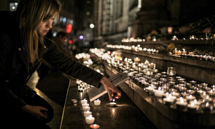 A woman lights a candle in tribute to the victims of Paris' attacks, on Nov. 14, 2015, in Terreaux quarter on the esplanade of Lyon town hall. (Jeff Pachoud/AFP/Getty Images)