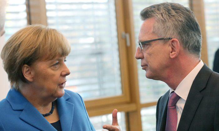 German Interior Minister Thomas de Maiziere (R) and German Chancellor Angela Merkel talk prior to a meeting of the executive committee of the conservative Christian Democratic Union (CDU) in Berlin on Nov. 9, 2015. (Wolfgang Kumm/AFP/Getty Images)