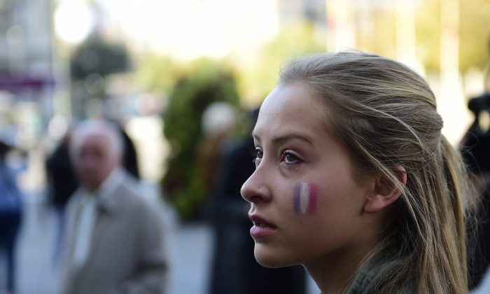 A young woman with a French flag painted on her face looks on during a minute of silence outside Madrid's town hall on Nov. 14, 2015, for victims and families following a series of terror attacks in the French city of Paris and its surroundings that has left at least 127 people dead and some 200 wounded. (Pierre-Philippe Marcou/AFP/Getty Images)