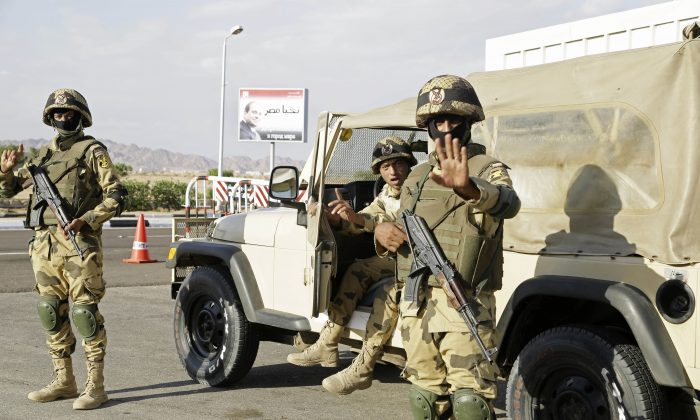 """Egyptian soldiers guarding the entrance to the Sharm el-Sheikh International Airport gesture to a photographer in south Sinai, Egypt, on Nov. 6, 2015. The sign has a picture of Egyptian President Abdel Fattah el-Sissi and a slogan in Arabic which reads, """"Long Live Egypt."""" Startling public criticism in Egypt points to how the aura of invincibility that President el-Sissi has long enjoy appears to be eroding. The criticisms spring from multiple fronts—complaints over neglect by officials, an economy that hasn't seen dramatic improvement and now worries over tourism following the crash of a Russian jet in Sinai. (AP Photo/Thomas Hartwell)"""