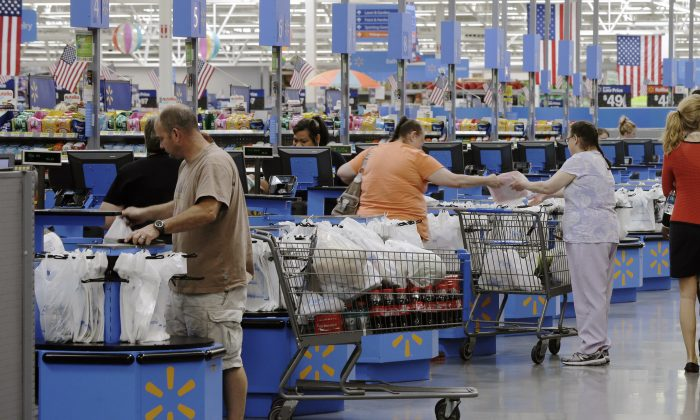 Shoppers check out at a Wal-Mart Supercenter store in Springdale, Ark., on June 4, 2015. The Commerce Department on Nov. 13, 2015, says retail sales rose a seasonally adjusted 0.1% last month, after being unchanged in September. (AP Photo/Danny Johnston)