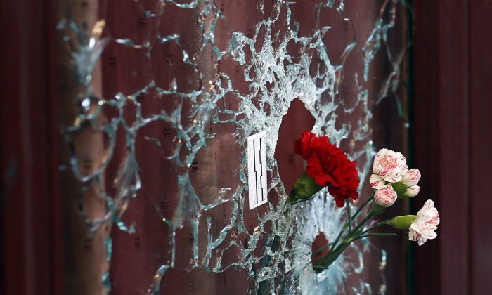 Flowers are set in a window shattered by a bullet at the Carillon cafe in Paris, France, on Nov. 15, 2015, two days after over 120 people were killed  in a series of shooting and explosions, including suicide bombers. (AP Photo/Jerome Delay)