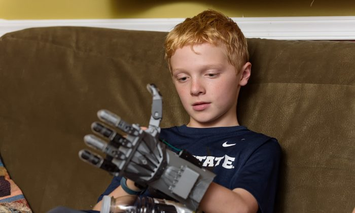 In this Oct. 22, 2015, photo, Colin Consavage, 10, of Claymont, Del., shows the prosthetic hand he made himself with a 3D printer at the local library. Colin was born with his left hand in a fist, the result of amniotic banding that kept one hand stunted. He used a 3-D printer at the Wilmington Public Library to make himself a mechanical replacement. (Doug Curran/The Wilmington News-Journal via AP)