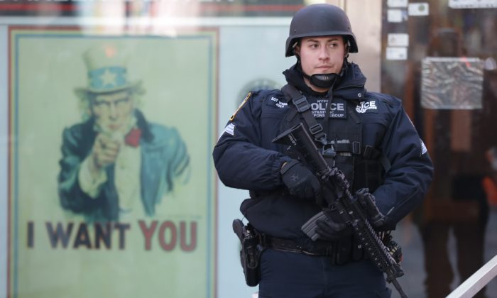 A heavily armed New York city police officer with the Strategic Response Group stands guard at the armed forces recruiting center in New York's Times Square, Saturday, Nov. 14, 2015.  (AP Photo/Mary Altaffer)