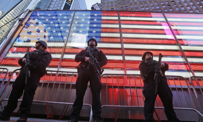 Heavily armed New York city police officers with the Strategic Response Group stand guard at the armed forces recruiting center in New York's Times Square, Saturday, Nov. 14, 2015. (AP Photo/Mary Altaffer)