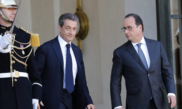 Former French President, Nicolas Sarkozy, leaves the Elysee Palace after a meeting with France's President, Francois Hollande (R) in Paris, Sunday, Nov. 15, 2015. (AP Photo/Jacques Brinon)