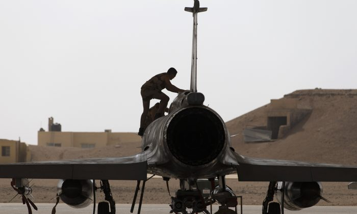 French army technicians inspect a Mirage 2000 fighter jet on October 12, 2015, during a visit by the French Prime Minister and the Defence Minister at an army base in Jordan where French army aircraft are based. French air strikes in Syria may have killed French jihadists, a source close to French Prime Minister Manuel Valls said, although the defence ministry said the information could not yet be confirmed. AFP PHOTO / KENZO TRIBOUILLARD        (Photo credit should read KENZO TRIBOUILLARD/AFP/Getty Images)
