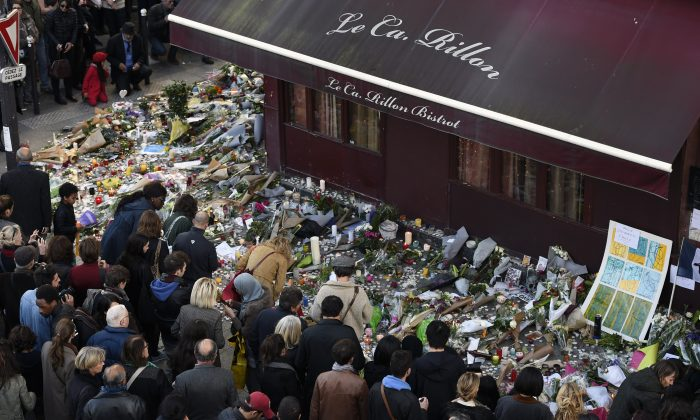 "People gather at a makeshift memorial in front of ""Le carillon"" restaurant on Nov. 16, 2015, in the 10th district of Paris, following a series of coordinated terrorists attacks on Nov. 13. (Alain Jocard/AFP/Getty Images)"