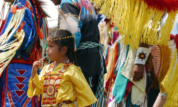 """URBANA, :  Five-year-old Tarlynn Tonepahhote of the Iowa Oneida Native American Indian tribe joins adult male dancers at the """"Grand Entry"""" start of a powwow in Urbana, Maryland, 04 August 2002. Powwows are a Native American celebrations where young and old gather to socialize and preserve native traditions by partaking in competitive singing and dancing contests for prize money.  According to the 1990 US Census figures, there are 1.87 million American Indians living in the United States.  AFP PHOTO/Robyn BECK (Photo credit should read ROBYN BECK/AFP/Getty Images)"""