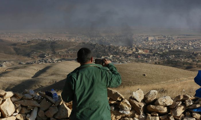 A Kurdish fighter records smoke rising over Sinjar, northern Iraq from oil fires set by Islamic State militants as Kurdish Iraqi fighters, backed by U.S.-led airstrikes, launch a major assault on Thursday, Nov. 12, 2015. The strategic town of Sinjar was overran last year by the Islamic State group in an onslaught that caused the flight of tens of thousands of Yazidis and first prompted the United States to launch the air campaign against the militants. (AP Photo/Bram Janssen)
