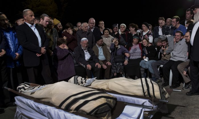 Relatives mourn during the funeral of Rabbi Ya'akov Litman and his son Netanel, in Jerusalem, Saturday, Nov. 14, 2015. Rabbi Ya'akov Litman and his son Netanel were killed in a shooting attack south of the West Bank city of Hebron. (AP Photo/Tsafrir Abayov)