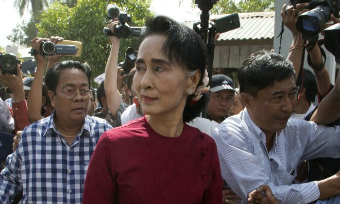 FILE - In this Sunday, Nov. 8, 2015, file photo, leader of Myanmar's National League for Democracy party, Aung San Suu Kyi visits a polling station on the outskirts Yangon, Burma. (AP Photo/Mark Baker, File)