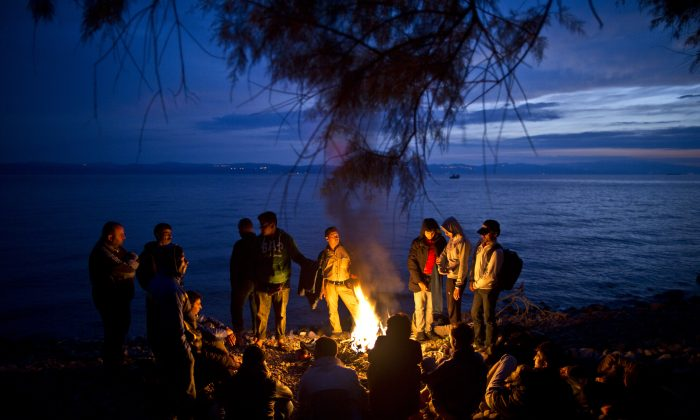 Syrian and Afghan refugees warm themselves and dry their clothes around a fire after arriving on a dinghy from the Turkish coast to the northeastern Greek island of Lesbos, on Oct. 7, 2015. (AP Photo/Muhammed Muheisen)