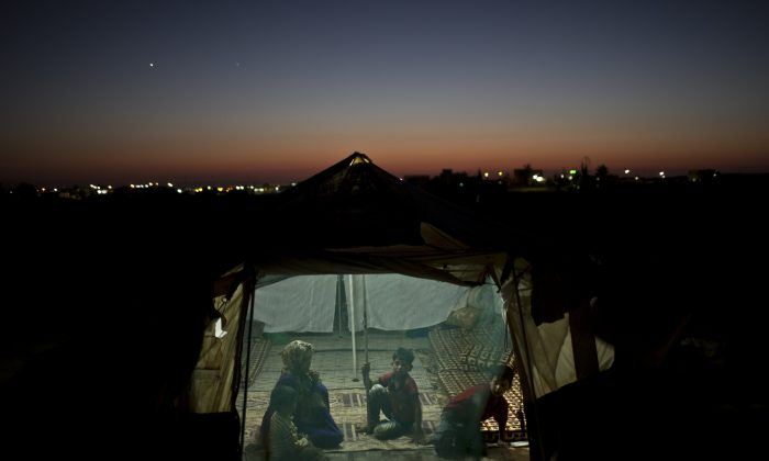 Syrian refugee Eidah Hassoun, 36, sits with her children inside their tent at an informal tented settlement near the Syrian border on the outskirts of Mafraq, Jordan, on July 22, 2015. (AP Photo/Muhammed Muheisen)