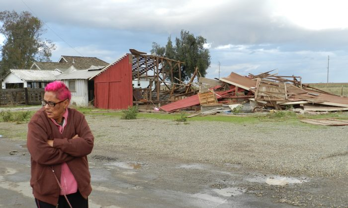 Sabina Woodard stands across the street from her destroyed barn after reports of a rare tornado in Denair, Calif., on Nov. 15, 2015. The National Weather Service said video and witness reports confirm a tornado touched down in Denair, which tore roofing and walls, knocked down trees and power lines and damaged gas lines. (Deke Farrow/The Modesto Bee via AP)
