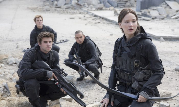 "This photo provided by Lionsgate shows, Liam Hemsworth, left, as Gale Hawthorne, Sam Clafin, back left, as Finnick Odair, Evan Ross, back right, as Messalia, and Jennifer Lawrence, right, as Katniss Everdeen, in the film, ""The Hunger Games: Mockingjay - Part 2.""  The movie opens in U.S. theaters on Nov. 20, 2015. (Murray Close/Lionsgate via AP)"