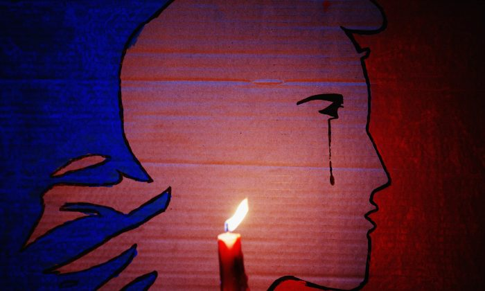 A candle burns during a vigil in Aotea Square to remember victims of the Paris attacks in Auckland, New Zealand, on Nov. 14, 2015. (Hannah Peters/Getty Images)