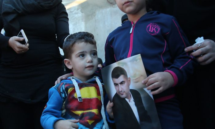 Ali (C-L) and Malak (C-R), the children of Adel Termos, who was killed in a twin bombing attack that rocked a busy shopping street in the area of Burj al-Barajneh in Beirut's southern suburb, carry a portrait of their father during his funeral in the village of Tallussa in the Nabatiyeh governorate, south of Lebanon on November 13, 2015. Lebanon mourned 44 people killed in south Beirut in a twin bombing claimed by the Islamic State group, the bloodiest such attack in years, the Red Cross also said at least 239 people were also wounded, several in critical condition. (MAHMOUD ZAYYAT/AFP/Getty Images)