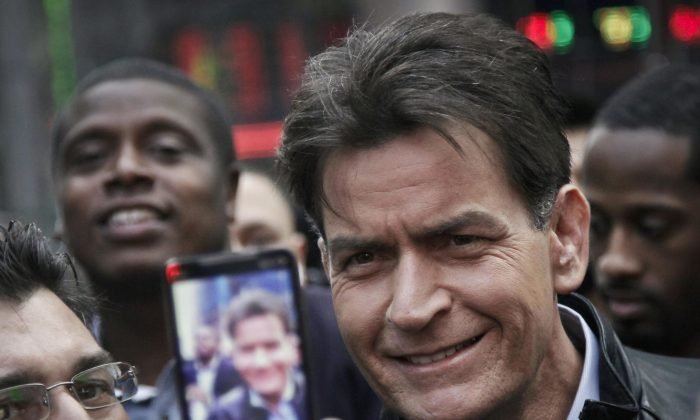 """Actor Charlie Sheen is mobbed for autographs and photos as he makes his way through Times Square in New York on Jan. 14, 2013. In an interview Tuesday, Nov. 17, 2015, on NBC's """"Today,"""" Sheen said he tested positive for the virus that causes AIDS. (AP Photo/Bebeto Matthews)"""