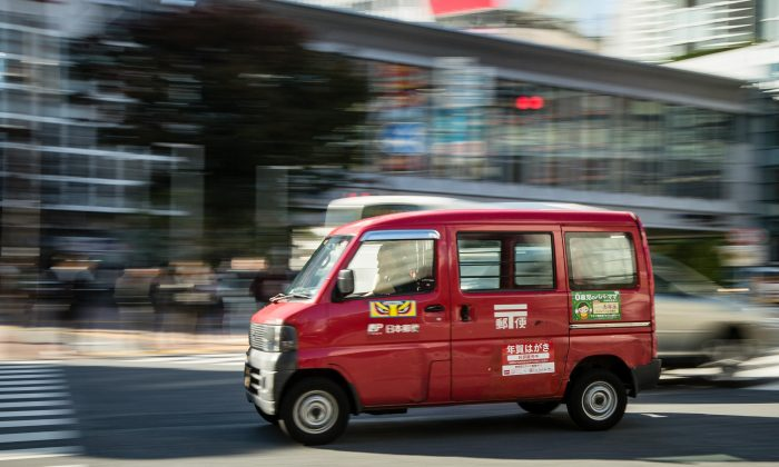 A Japan Post delivery van is seen driving along a road in downtown Tokyo, Japan, on Nov. 4, 2015. (Christopher Jue/Getty Images)