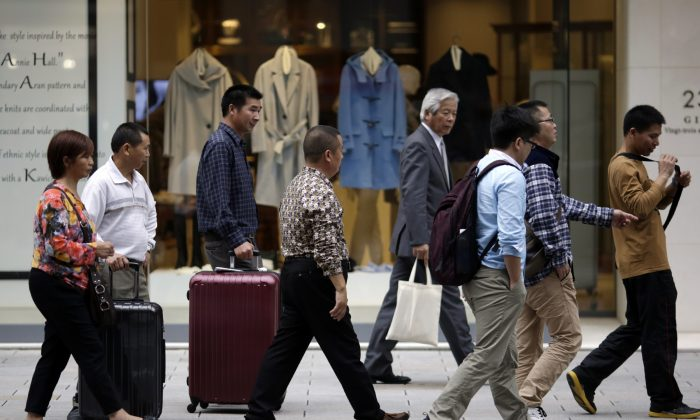 Foreign shoppers walk at a shopping district in Tokyo, Tuesday, Nov. 17, 2015. Japan, the world's third-largest economy, is highly dependent on the health of other economies, such as the U.S. and China, to keep growth going because much of the Japanese economy is export-led. One concern is that China's growth is gradually slowing. (AP Photo/Eugene Hoshiko)