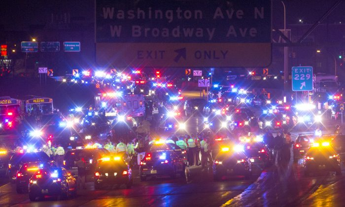 Demonstrators are surrounded and arrested by police after blocking a portion of Interstate 94, shutting down the northbound lanes, Monday, Nov. 16, 2015, in Minneapolis. The mayor of Minneapolis on Monday asked for a federal civil rights investigation into the weekend shooting of a black man by a police officer during an apparent struggle. Community members and activists called for a federal investigation, as well as for authorities to release video of the incident and the officer's identity. (Carlos Gonzalez/Star Tribune via AP)
