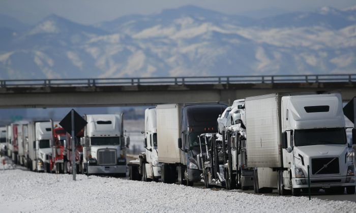 A long line of tractor trailers sit and wait at a roadblock along Interstate 70 as a winter storm packing high winds and snow blankets the plains Tuesday, Nov. 17, 2015, in Aurora, Colo. The storm has closed much of Interstate 70, Colorado's main east-west highway, because of blizzard conditions on the Eastern Plains as well as in northwest Kansas. (AP Photo/David Zalubowski)