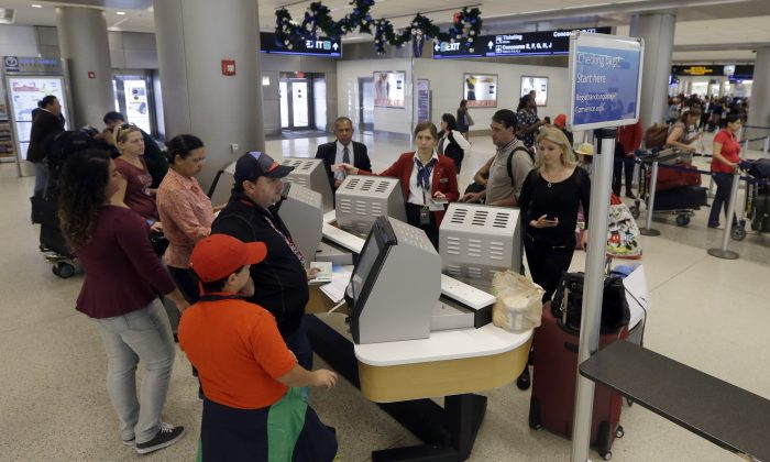 Travelers check in their luggage as they prepare to travel at Miami International Airport in Miami on Nov. 25, 2015. A stronger economy and lower gas prices means Thanksgiving travelers can expect more highway congestions in 2015. Airlines for America, the lobbying group for several major airlines, forecasts 25.3 million passengers will fly on U.S. airlines, up 3% from last year. (AP Photo/Alan Diaz)
