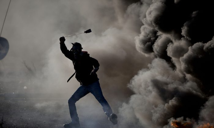 A Palestinian swings a sling during clashes with Israeli troops, in the West Bank city of Ramallah, on Nov. 13, 2015. (AP Photo/Majdi Mohammed)