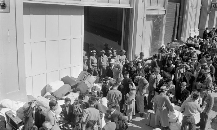 As military police stand guard, people of Japanese descent wait at a transport center in San Francisco April 6, 1942 for relocation to an internment center at Santa Anita racetrack near Los Angeles. They were among thousands of people forced from their homes in the name of national security following the attack on Pearl Harbor. (AP Photo)