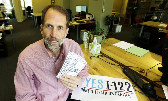 Alan Durning, author of an initiative passed by Seattle voters that created the nation's first voucher system for campaign contributions, poses for a photo in his office in Seattle while holding an artist's depiction of a possible design for the vouchers, on Nov. 12, 2015. (AP Photo/Ted S. Warren)