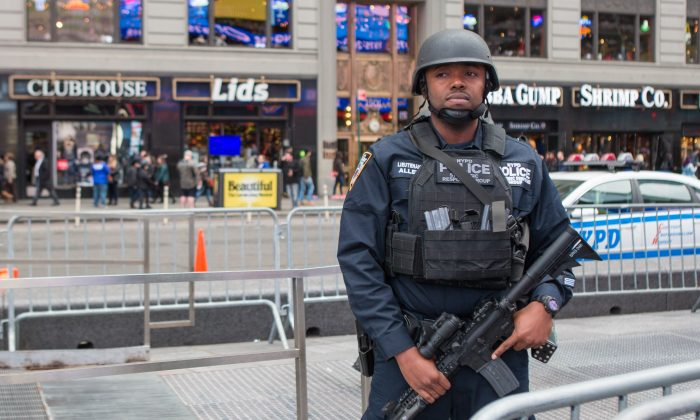 A member of the NYPD Strategic Response Group stands guard in New York's Times Square on Nov. 18, 2015. Police officials said they've deployed extra units to crowded areas of the city in the wake of the Paris terror attacks. (Benjamin Chasteen/Epoch Times)