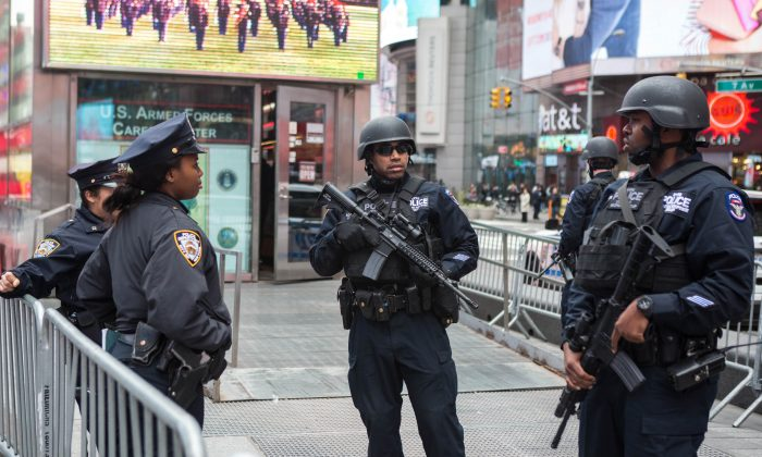 Members of the NYPD Strategic Response Group and an NYPD officer stand guard in New York's Times Square on Nov. 18, 2015. Police officials said they've deployed extra units to crowded areas of the city in the wake of the Paris terror attacks. (Benjamin Chasteen/Epoch Times)