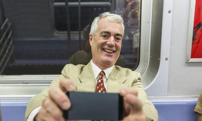 Senior Businessman Taking a Selfie in the Subway Train