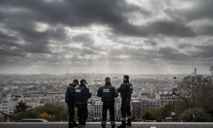 French Police officers stand on guard near the church of Sacre Coeur, on top of the Montmartre Hill, overviewing Paris, on Nov. 18, 2015. (AP Photo/Daniel Ochoa de Olza)