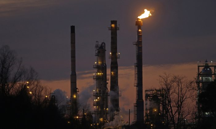 FILE - In this Feb. 13, 2015, file photo, stacks and burn-off from the Exxon Mobil refinery are seen at dusk in St. Bernard Parish, La. Corporate America has a profit problem. U.S company earnings are falling for the first time since 2009, when the economy was still reeling from the Great Recession. The main culprit is the plunging price of oil, which has decimated earnings at big energy companies like Exxon Mobil and Chevron. (AP Photo/Gerald Herbert, File)