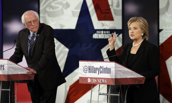 In this Nov. 14, 2015, photo, Hillary Rodham Clinton, right, makes a point as Bernie Sanders listens during a Democratic presidential primary debate in Des Moines, Iowa. (AP Photo/Charlie Neibergall)