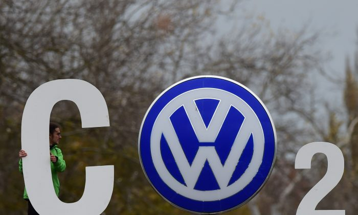 "An activist of environmental organisation Greenpeace holds a giant letter to display ""CO2"" around the logo of German car maker Volkswagen ( VW ) at the entrance of the company's headquarters in Wolfsburg, on November 9, 2015. (John Macdougall/AFP/Getty Images)"