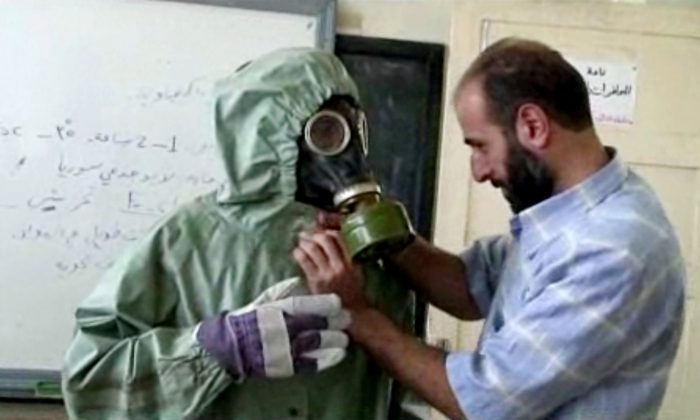 FILE - This image made from an AP video posted on Wednesday, Sept. 18, 2013 shows a volunteer adjusting a students gas mask and protective suit during a session on reacting to a chemical weapons attack, in Aleppo, Syria.