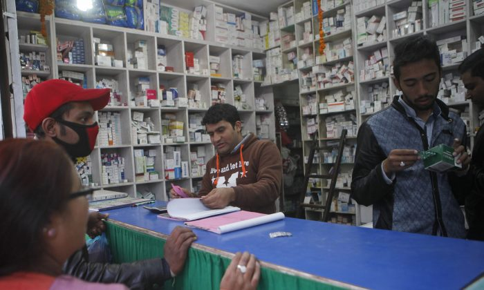 Nepalese people, left, wait to buy medicines at a chemist shop in Kathmandu, Nepal, Thursday, Nov. 19, 2015. (AP Photo/Niranjan Shrestha)