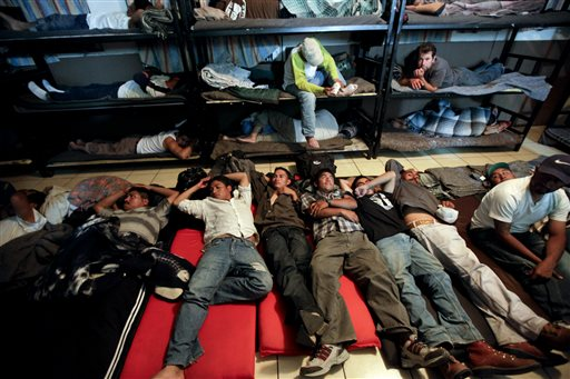 In this April 28, 2010, file photo, men look for a place to sleep in a crowded shelter for migrants deported from the United States, in the border city of Nogales, Mexico. (AP Photo/Gregory Bull)