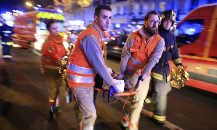 In this Nov.13, 2015 file photo, a woman is being evacuated from the Bataclan concert hall after a shooting in Paris. (AP Photo/Thibault Camus)