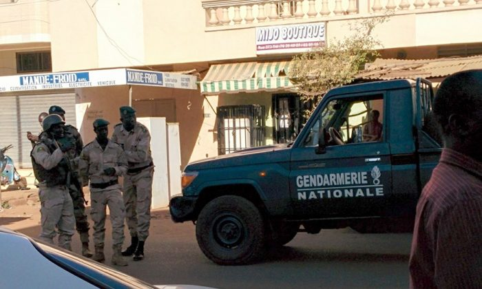 In this image made available by Malikahere.com security personnel, attend close to the scene of an attack on a hotel in Bamako, Mali Friday Nov. 20, 2015. (Malikahere.com via AP)