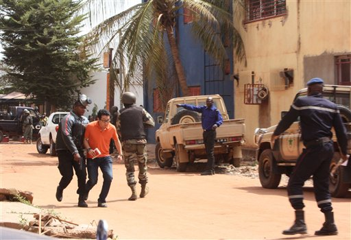 A Mali trooper, left, assist a hostage, second left, to leave the scene, from the Radisson Blu hotel to safety after gunmen attacked the hotel in Bamako, Mali, Friday, Nov. 20, 2015. (AP Photo/Harouna Traore)