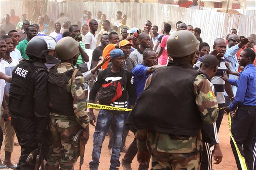Mali troops try to control a crowd of onlookers near the  Radisson Blu hotel, after an attack by gunmen on the hotel in Bamako, Mali, Friday, Nov. 20, 2015. Islamic extremists armed with guns and grenades stormed the luxury Radisson Blu hotel in Mali's capital Friday morning, and security forces worked to free guests floor by floor.  (AP Photo/Harouna Traore)